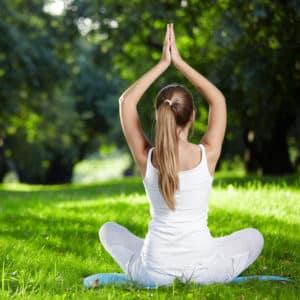 Eine Frau, die meditiert bzw. Yoga Übungen ausführt