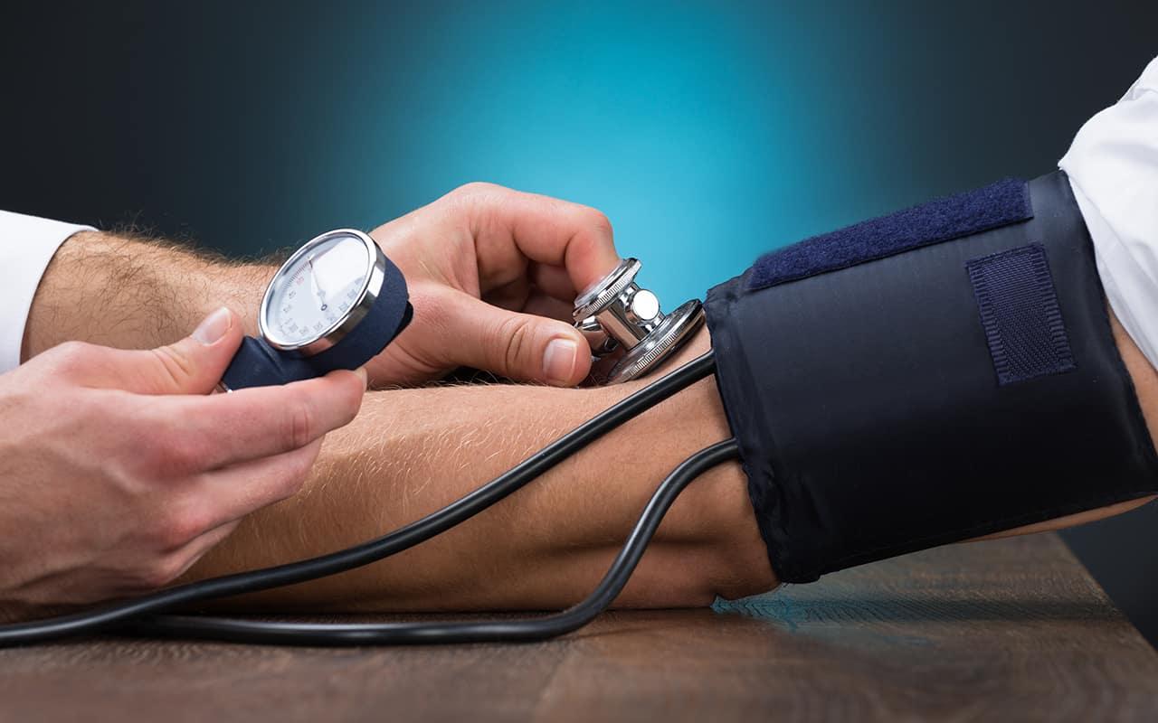 Ein Arzt misst den Blutdruck am Arm