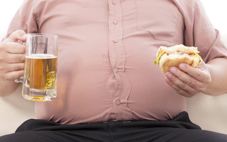 Ein dicker Mann mit einem Bier und einem Burger in der Hand