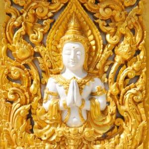 Ein Relief eines weißen Buddhas in gold gefasst - Ein Symbol für die Tibetische Medizin