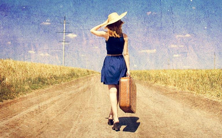 Eine attraktive Frau mit Reisekoffer auf einer Landstrasse im Vintage Stiel, Sie hat einen langen Rücken als Symbol für ein Leben ohne Rückenschmerzen