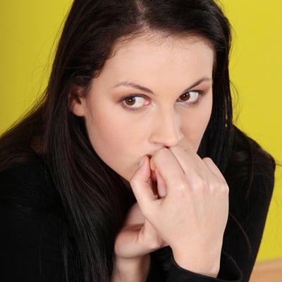 Eine Frau, die sitzt und ängstlich schaut