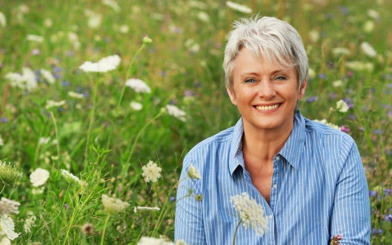 Eine attraktive ältere Frau auf einer grünen Wiese