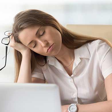 Eine müde Frau am Laptop