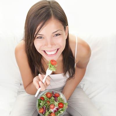 Eine atraktive Frau beim Essen, mit einer Schüssel Salat in der Hand
