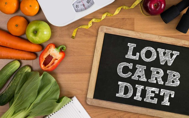 Ein Tisch mit Gemüse und einem Schild mit der Aufschrift Low Carb Diät
