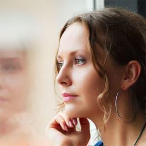 Eine Frau, die nachdenklich aus einem Fenster sieht