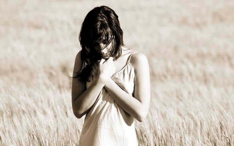Eine Frau, die sich die Hände vor das Herz hält und starke Emotionen erlebt als Symbol für Psychosomatik