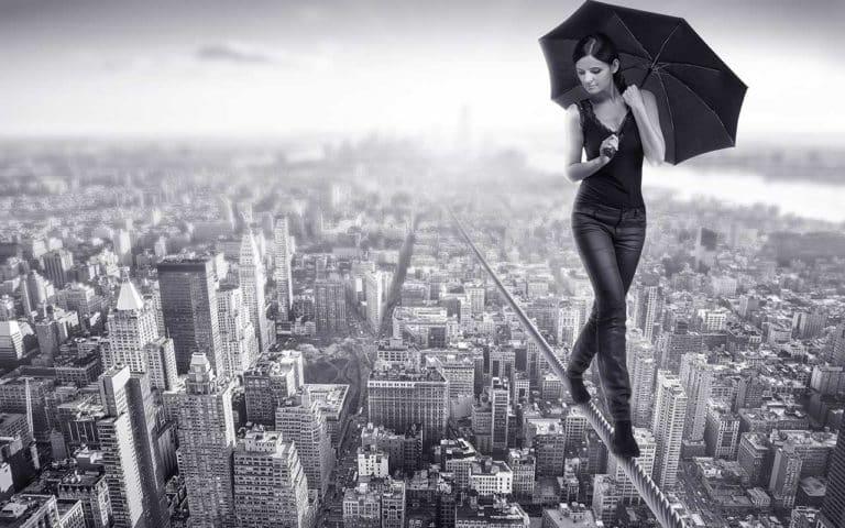 Eine Frau, die über einer Stadt auf einem Drahtseil balanciert als Symbol für Angst bei Albträumen