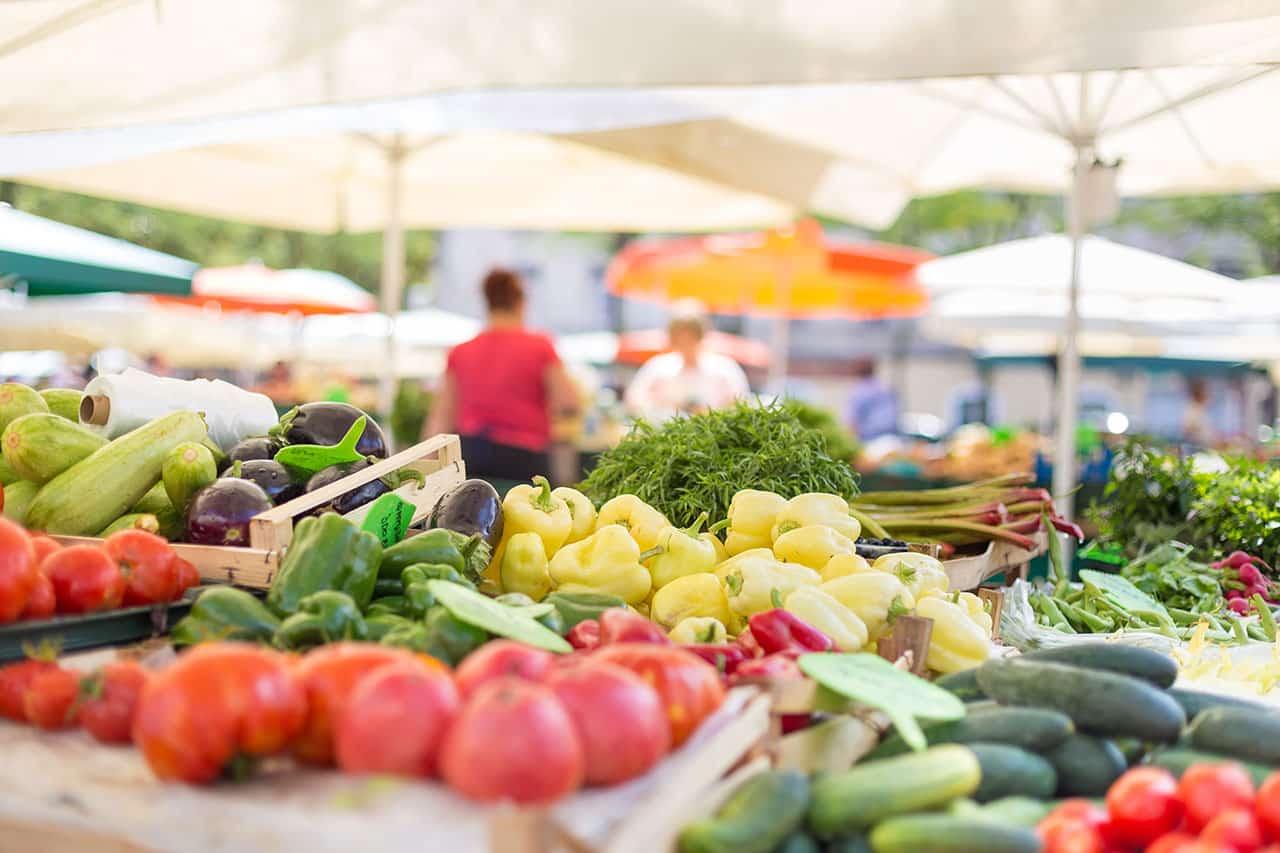 Eine Person auf einem Gemüsemarkt, viel Gemüse und Lebensmittel im Vordergrund
