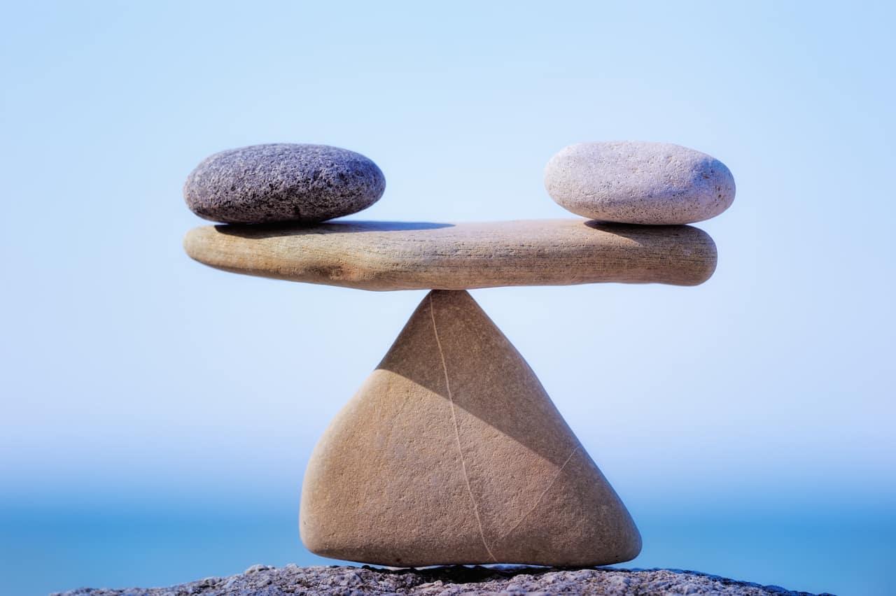 Eine Waage aus Steinen, im Hintergrund das Meer