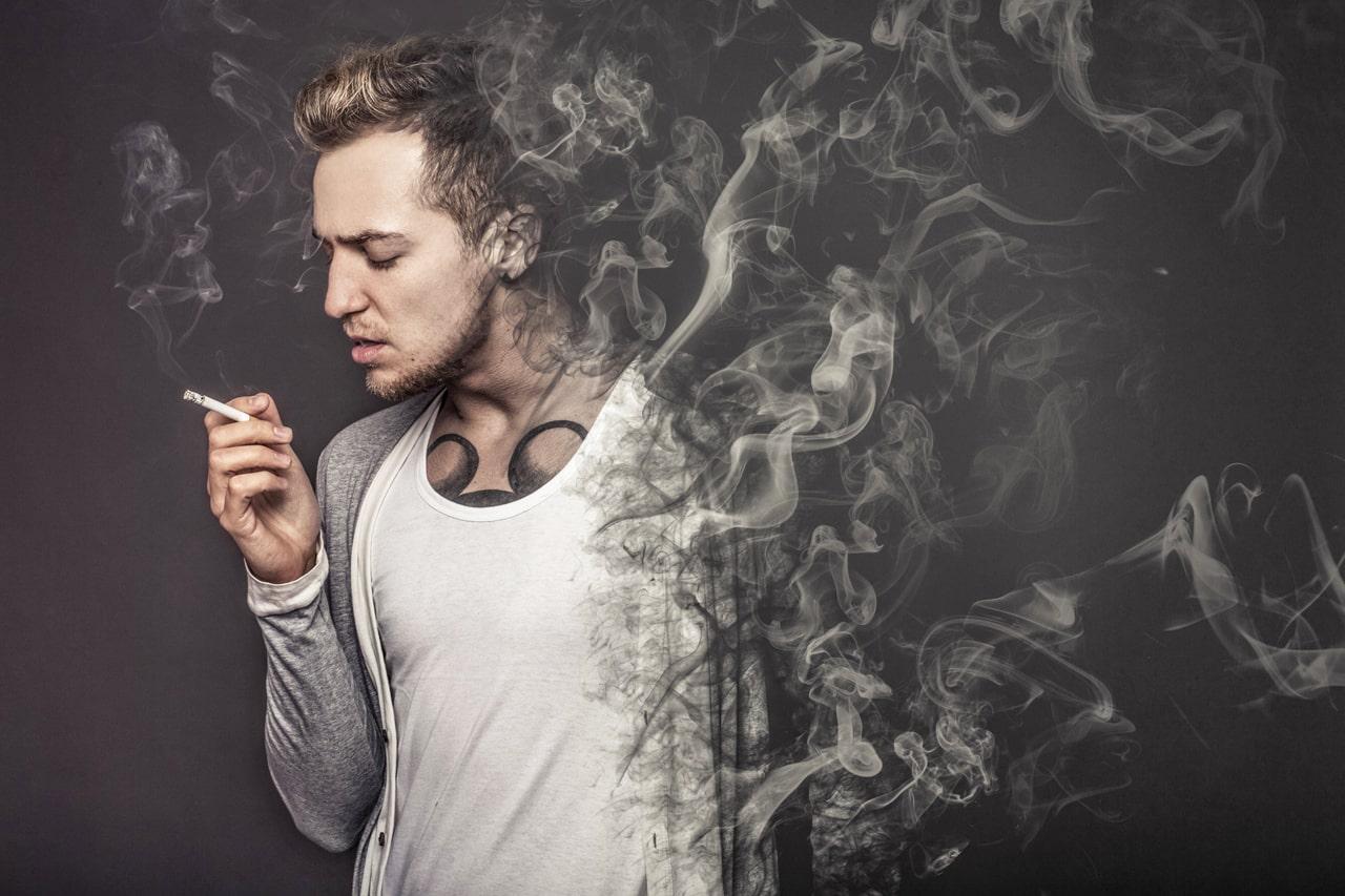 Ein Zigarette rauchender Mann, der sich in Rauch auflöst