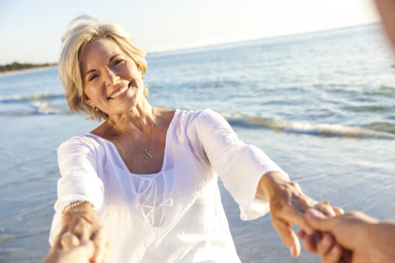 Eine ältere Frau am Meer wird an den Händen gehalten